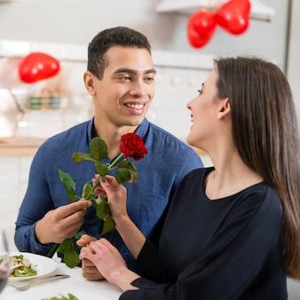 Mann, der seiner schönen freundin am valentinstag eine rose gibt