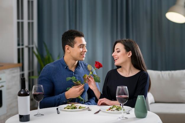 Mann, der seiner schönen freundin eine rose gibt