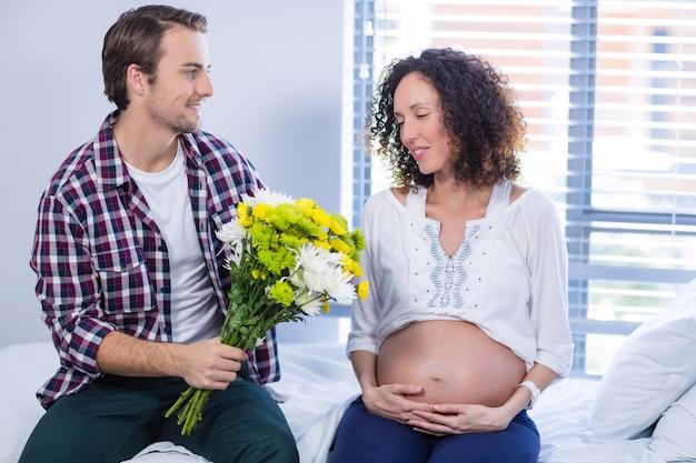 Mann, der seiner schwangeren frau auf der station blumenstrauß anbietet