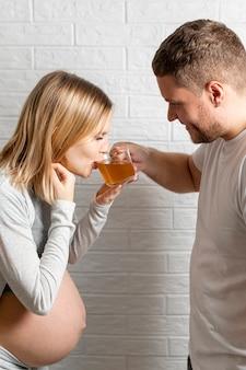 Mann, der seiner schwangeren frau einen tee anbietet