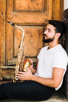 Mann, der seitlich mit saxophon sitzt