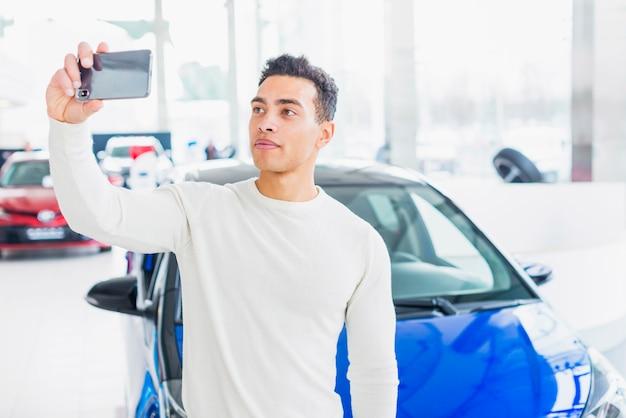 Mann, der selfie im autohaus nimmt
