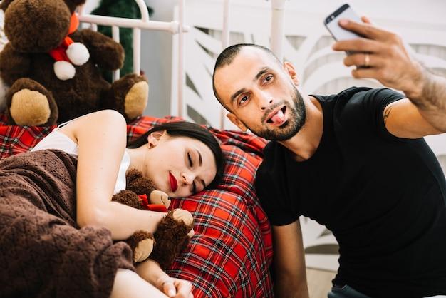Mann, der selfie nahe schlafender frau nimmt