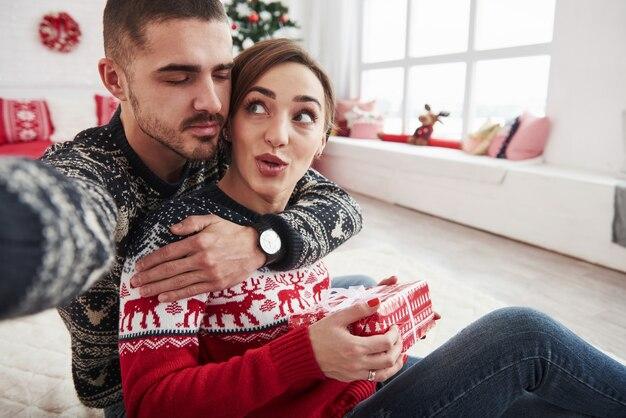 Mann, der selfie von ihm und seiner frau nimmt, die in der weihnachtskleidung gekleidet sind und auf dem boden des dekorativen schönen zimmers sitzen.