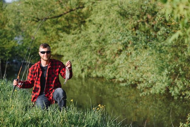 Mann, der sich am see entspannt und fischt