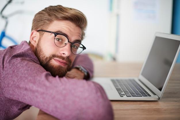 Mann, der sich auf den schreibtisch im büro stützt