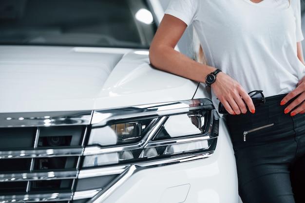 Mann, der sich auf fahrzeug stützt. partikelansicht des modernen weißen luxusautos, das tagsüber drinnen geparkt wird