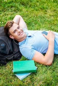 Mann, der sich auf gras entspannt. draufsicht auf einen gutaussehenden jungen mann, der die hand hinter dem kopf hält und lächelt, während er auf gras liegt und mp3-player hört