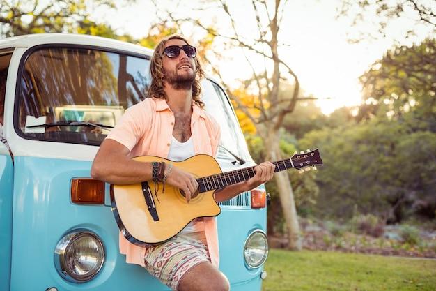 Mann, der sich auf wohnmobil stützt und gitarre spielt