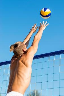 Mann, der sich darauf vorbereitet, eingehenden volleyball über das netz zu schlagen