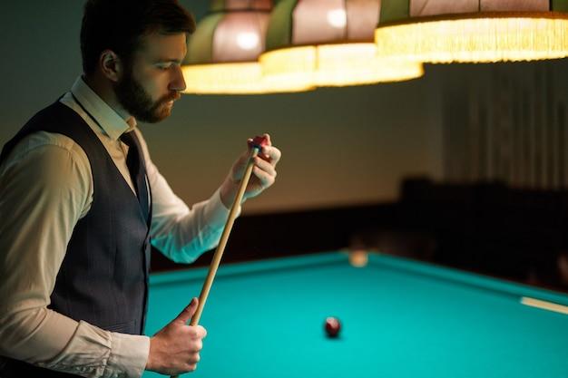 Mann, der sich darauf vorbereitet, professionelles billard im dunklen billardclub zu spielen, verbringt angenehme zeit
