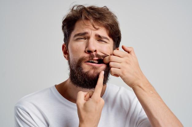 Mann, der sich festhält, um schmerzen in den zähnen zu sehen, isolierte hintergrund