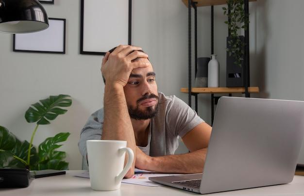 Mann, der sich gelangweilt fühlt, während er von zu hause aus arbeitet
