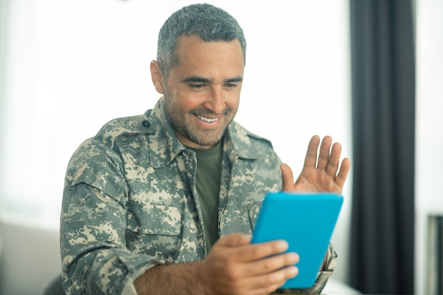 Mann, der sich glücklich fühlt. militärmann in uniform, der sich glücklich fühlt, während er seine familie auf dem bildschirm sieht