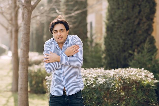 Mann, der sich in einem hemd im park kalt fühlt. foto in hoher qualität