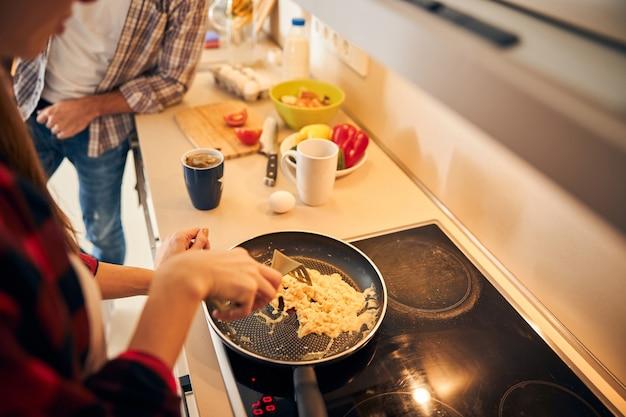 Mann, der sich neben einer köchin auf die arbeitsplatte stützt