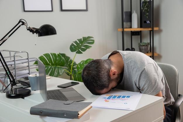Mann, der sich schläfrig fühlt, während er von zu hause aus arbeitet