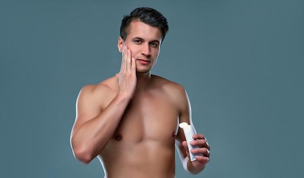 Mann, der sich um seine hygiene auf einem grauen raum kümmert