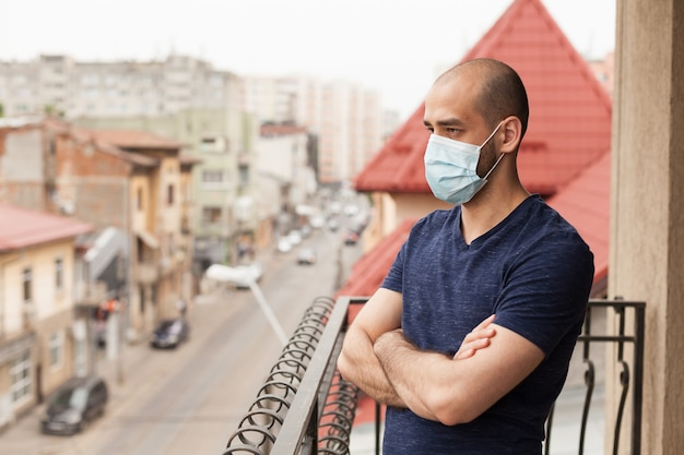 Mann, der sich während des ausbruchs des coronavirus auf dem balkon entspannt.