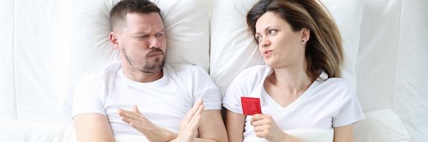 Mann, der sich weigert, sex mit einer frau mit kondom-draufsicht zu haben, sicheres konzept für sexuelle beziehungen