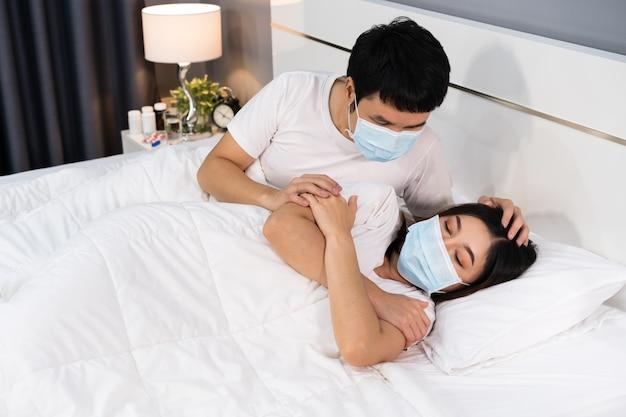 Mann, der sich zu hause um seine kranke frau im bett kümmert, paar, das medizinische maske zum schutz der coronavirus-pandemie trägt