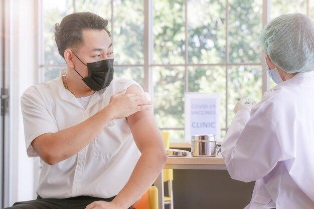 Mann, der sitzt, um einen covid-impfstoff in einer klinik oder einem krankenhaus zu bekommen, während eine handkrankenschwester den impfstoff vorbereitet