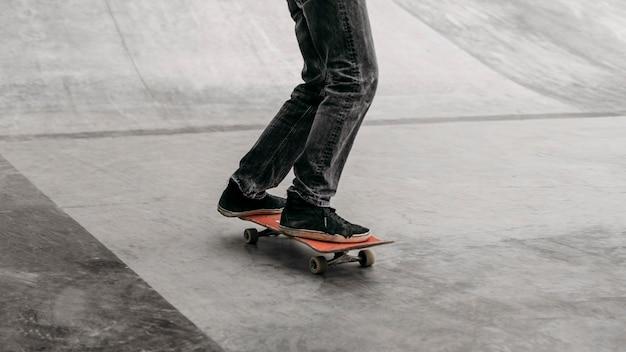 Mann, der skateboard im stadtpark reitet
