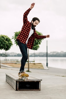 Mann, der skateboardtricks auf einer bank tut