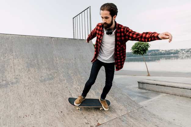 Mann, der skateboardtricks auf rampen tut