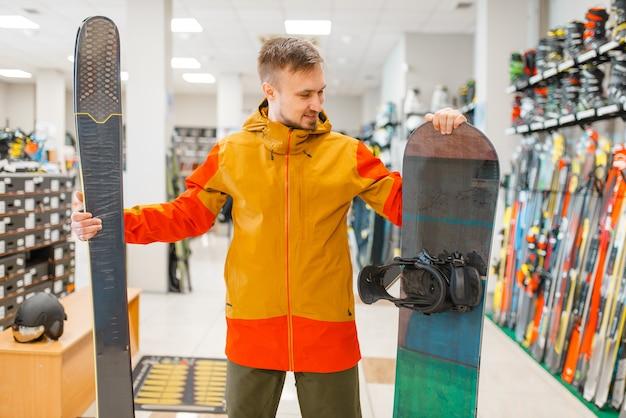 Mann, der skifahren und snowboard wählt, einkaufen im sportgeschäft.