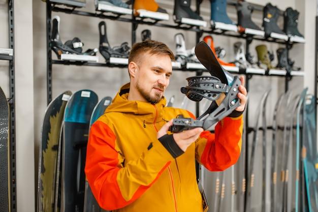 Mann, der skischuhbefestigung wählt, einkaufen im sportgeschäft.