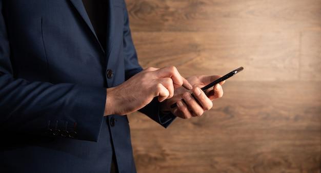 Mann, der smartphone auf hölzernem hintergrund hält