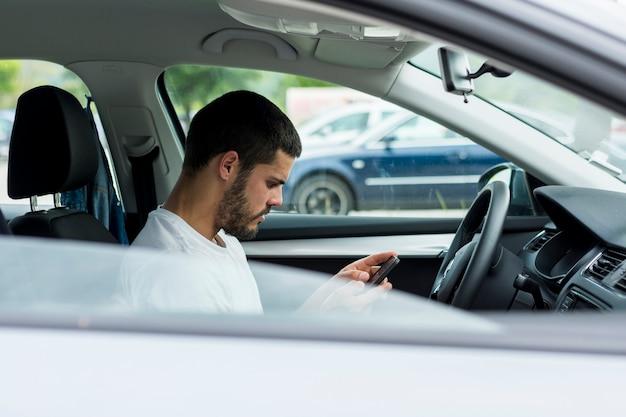 Mann, der smartphone beim sitzen im auto verwendet