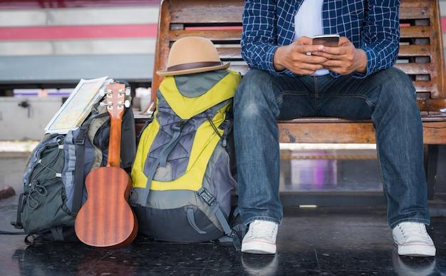 Mann, der smartphone beim warten auf zug verwendet