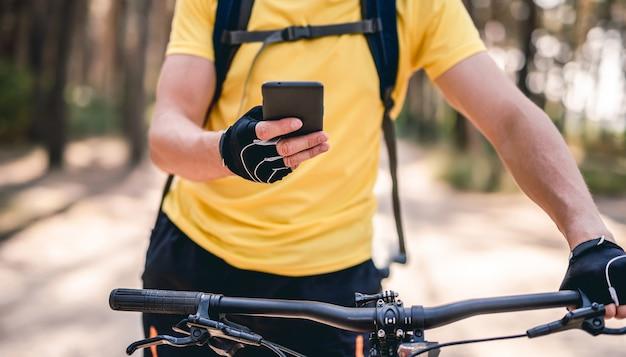 Mann, der smartphone für die navigation während der fahrradfahrt verwendet