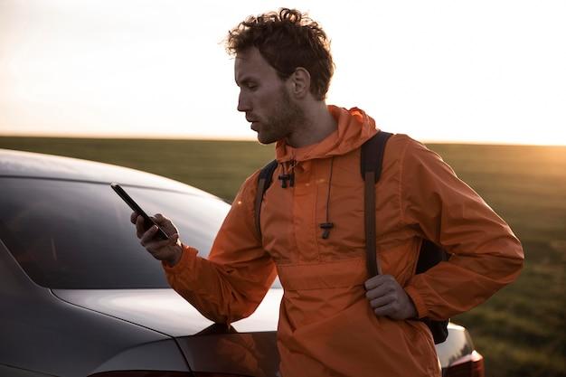 Mann, der smartphone im freien während auf einer straßenreise verwendet