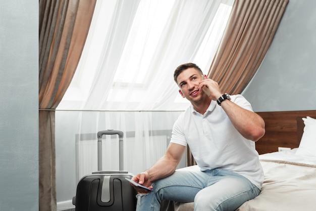 Mann, der smartphone im hotelzimmer verwendet