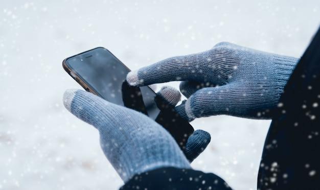 Mann, der smartphone im winter mit handschuhen für touchscreens verwendet