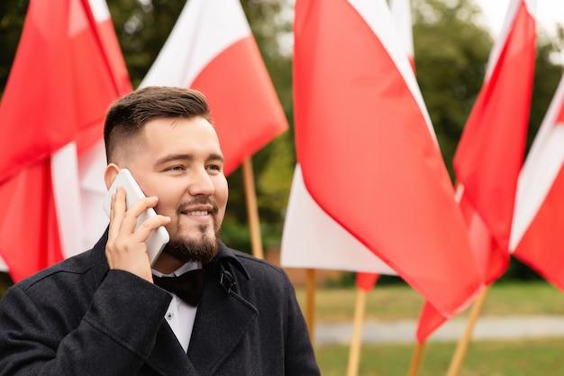 Mann, der smartphone mit flaggen von polen hinter sich hält