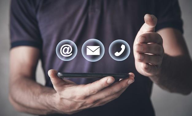 Mann, der smartphone mit kontaktsymbolen hält.
