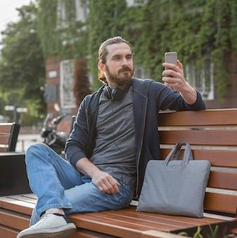 Mann, der smartphone mit laptoptasche in der stadt hält