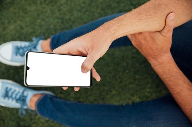 Mann, der smartphone mit modell hält