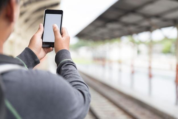 Mann, der smartphone mit rucksack am bahnhof hält