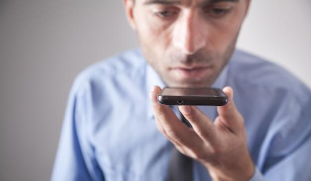 Mann, der smartphone unter verwendung der spracherkennung spricht.