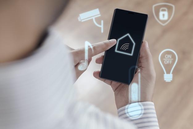 Mann, der smartphone verwendet, um smart home zu steuern
