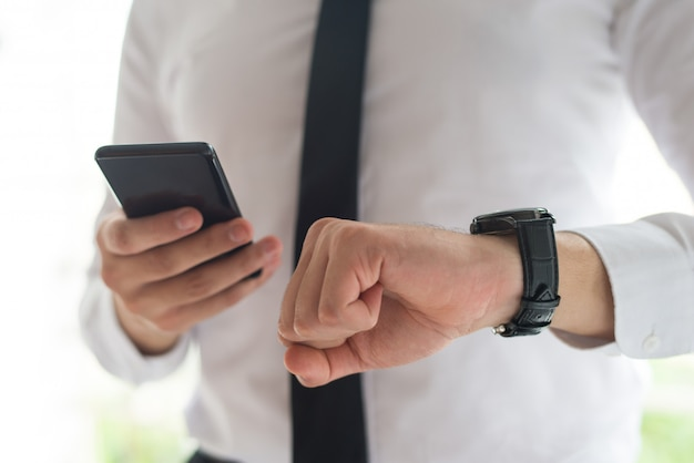 Mann, der smartphone verwendet und zeit überprüft
