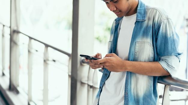 Mann, der smartphone, während der freizeit verwendet. das konzept der verwendung des telefons ist im alltag unerlässlich.