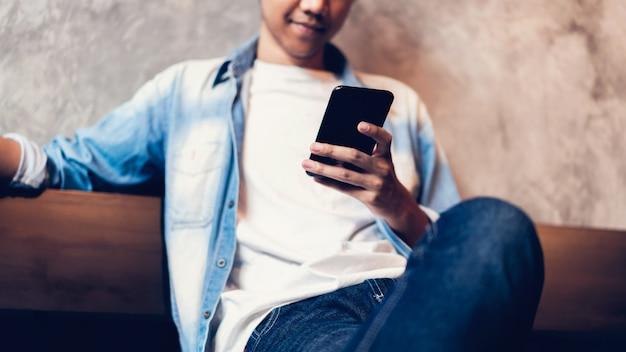 Mann, der smartphone, während der freizeit verwendet. das konzept der verwendung des telefons ist im täglichen leben von wesentlicher bedeutung.