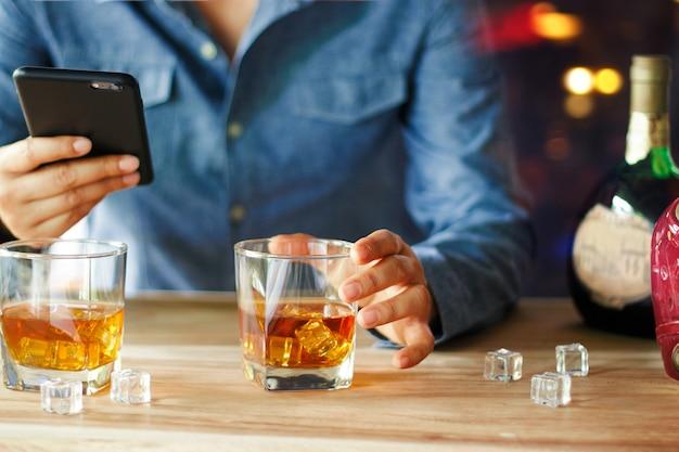 Mann, der smartphone während getränk des alkoholischen getränks des whiskys am barzähler verwendet
