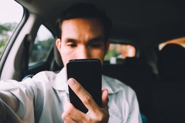 Mann, der smartphone zum einkaufs- und spielspielen verwendet und e-mail liest
